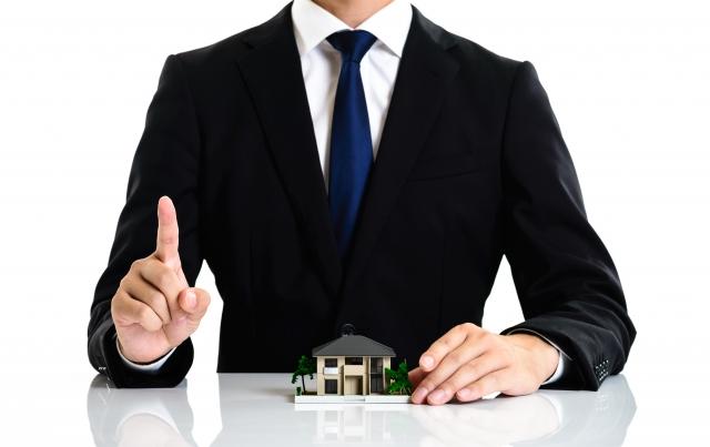 ビジネスマンとミニチュアの家